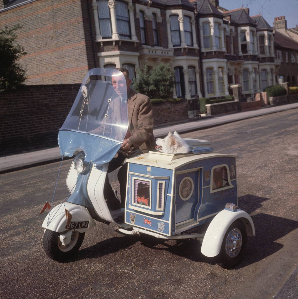 July 1962:  Charles Tumbridge riding his scooter through the streets of Kensal Rise, London, with his pet dog susie in his mobile kennel.  (Photo by Frank Martin/BIPs/Getty Images)