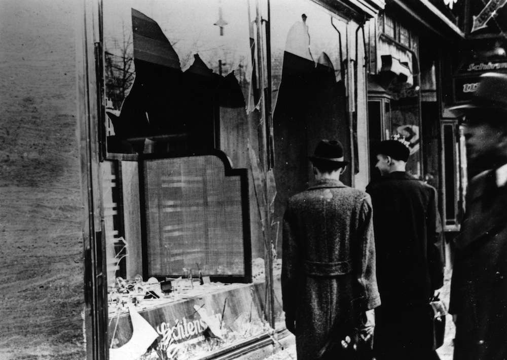 10th November 1938: Three onlookers at a smashed Jewish shop window in Berlin following riots of the night of 9th November. (Photo by Hulton Archive/Getty Images)