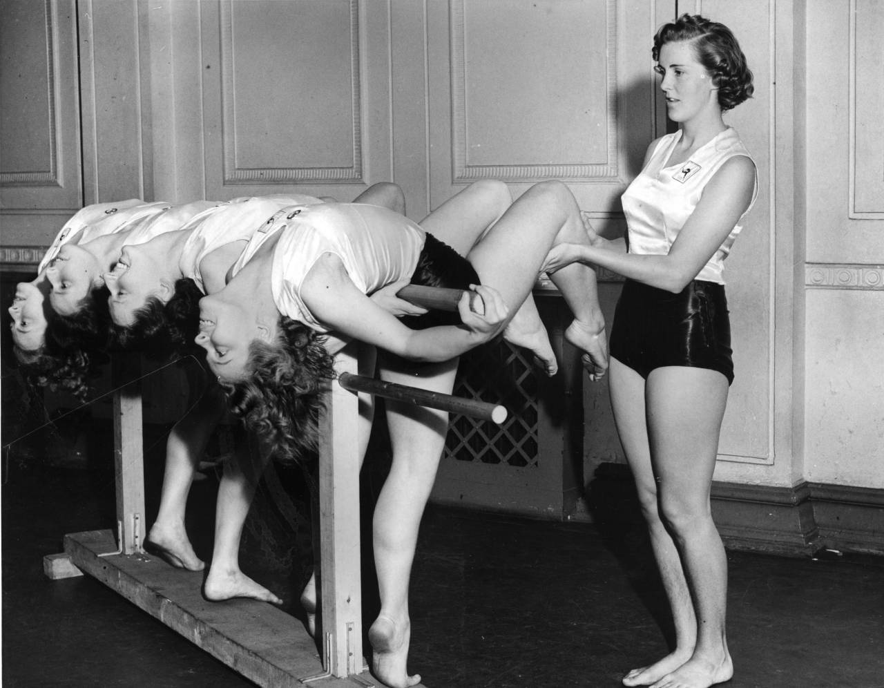 28th August 1940: Four teachers of the Womens' League of Health and Beauty stretch over an exercise bar. They are being instructed by Lady Prunella Hamilton at a summer refresher course in London. (Photo by William Vanderson/Fox Photos/Getty Images)