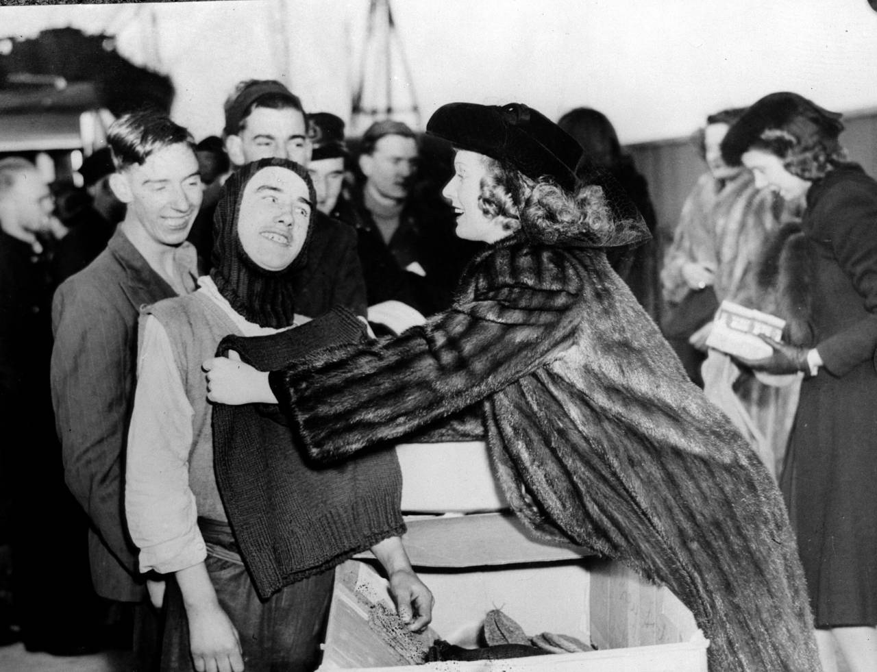 17th January 1941:  British film star Anna Neagle (1904 - 1986) helps a crew member of a British freighter try on a balaclava, gifts from the British War Relief Society of Brooklyn.  (Photo by Fox Photos/Getty Images)