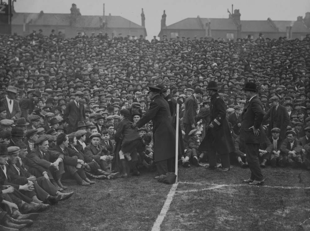 18th February 1928:  Police regulate the crowd at the touchline as great numbers of spectators crowd the pitch at Highbury in London for the cup tie battle between Arsenal and Aston Villa.  (Photo by Davis/Topical Press Agency/Getty Images)