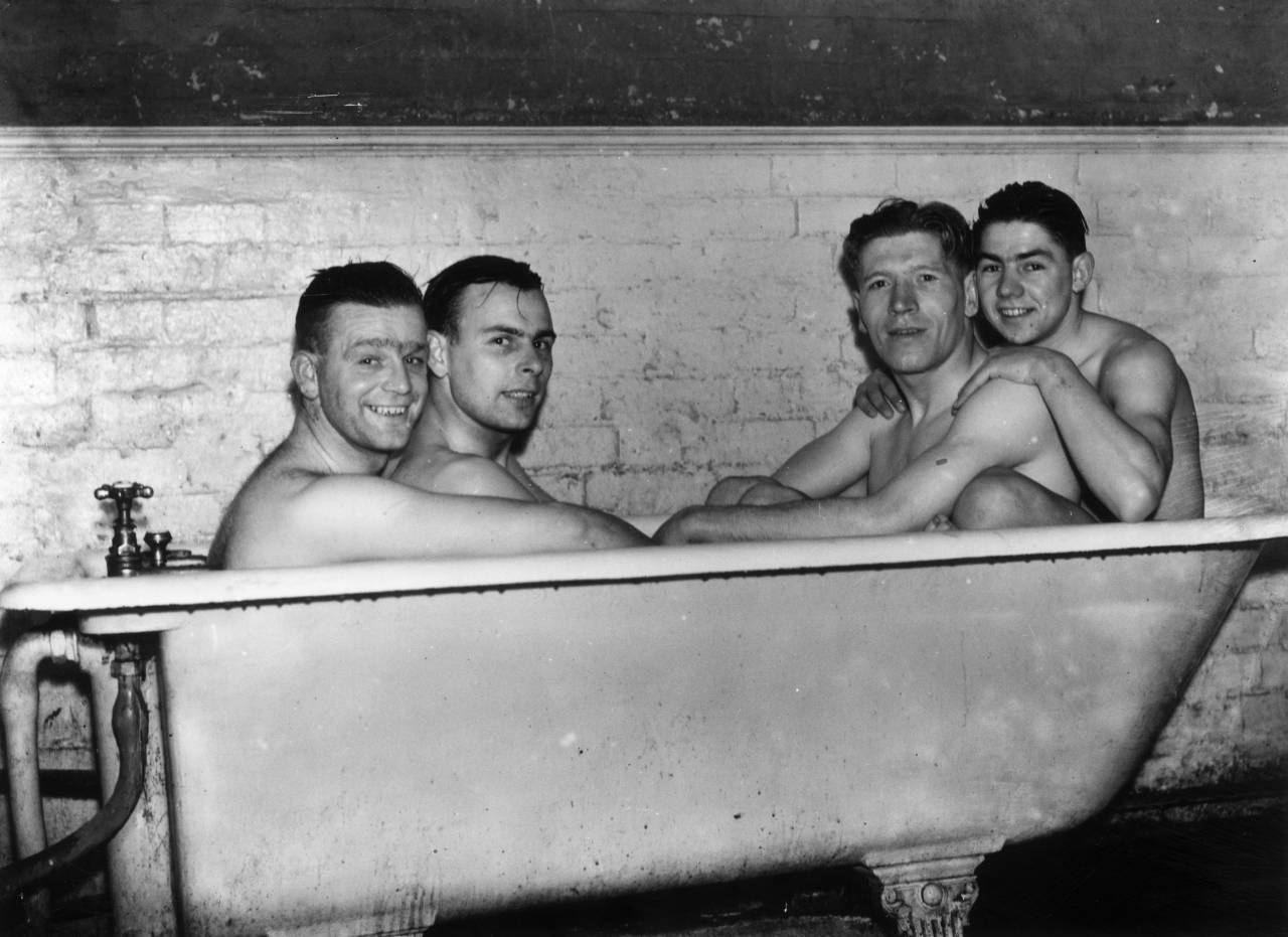26th January 1937: Poyser, MacKenzie, McCulloch and Smith of Brentford Football Club share a cramped bath after a hard training session at Bushey Hall, Hertfordshire, in preparation for their FA Cup tie match against Derby County on Saturday. (Photo by G. Adams/Topical Press Agency/Getty Images)