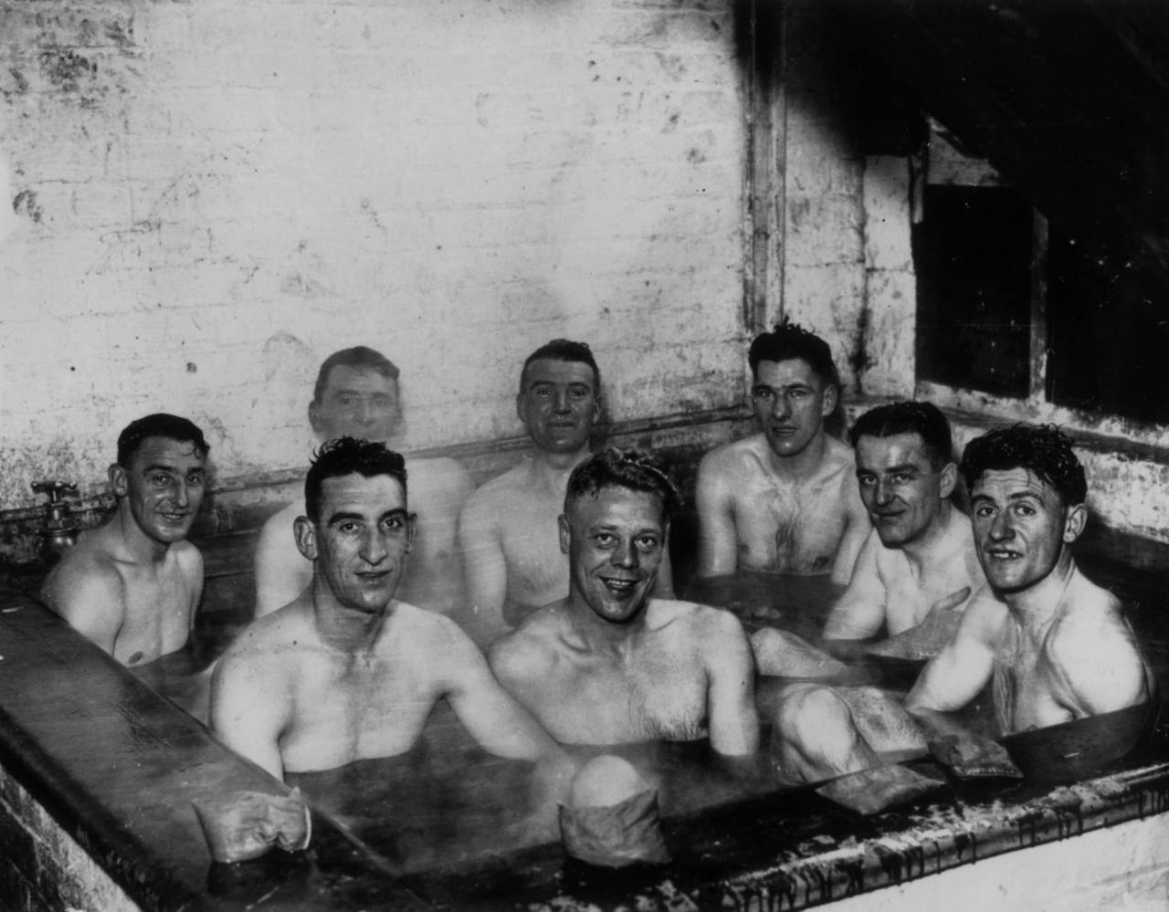 26th November 1937:  Scarborough footballers enjoying a seaweed bath during preparations for an FA Cup match.  (Photo by Fox Photos/Getty Images)