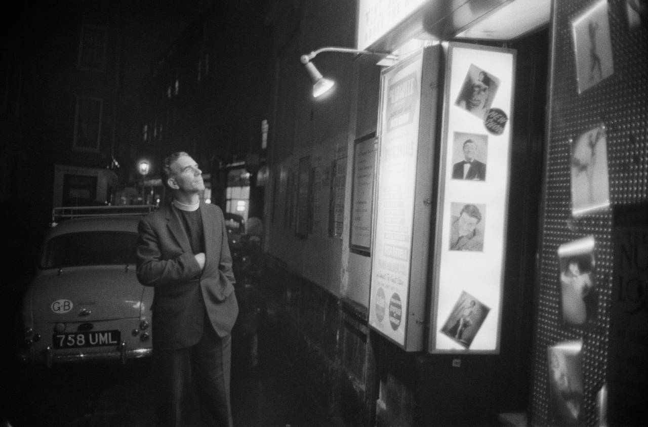 The reverend Vernon Mitchell inspects the images outside a strip club to determine what should be censored, Soho, London, 1st November 1960. (Photo by Peter Dunne/Daily Express/Hulton Archive/Getty Images)