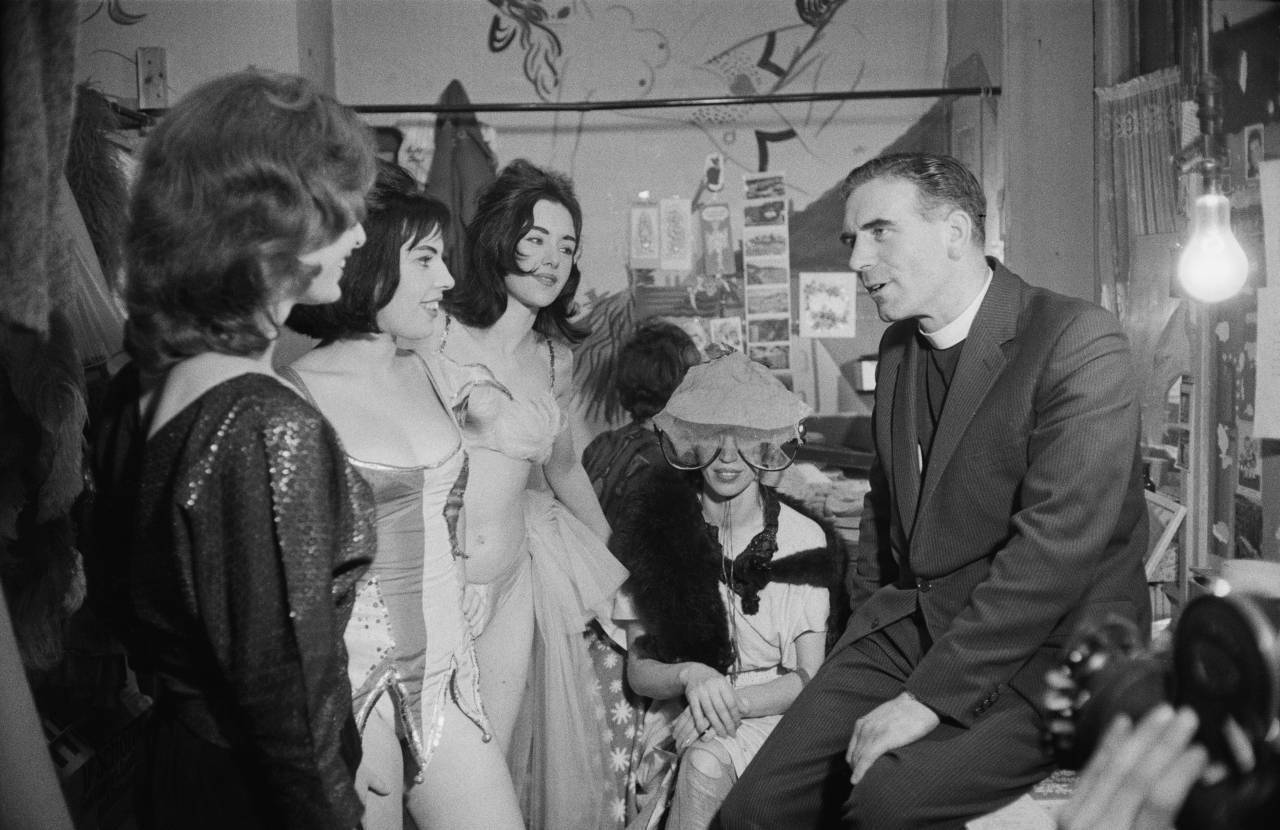 The reverend Vernon Mitchell talks to women at a strip club as part of a process to determine which segments of the show should be censored, London, 1st November 1960.