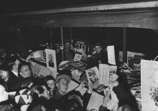 "German students gather around books they regard as ""un-German."" The books will be publically burned at Berlin's Opernplatz. Berlin, Germany, May 10, 1933.  — National Archives and Records Administration, College Park, Md."