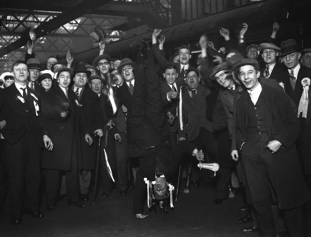 An Arsenal fan performs a one handed handstand at Euston Station to entertain his fellow supporters on their way to Birmingham for the F A Cup replay, 29th January 1930. (Photo by S. R. Gaiger/Topical Press Agency/Getty Images)