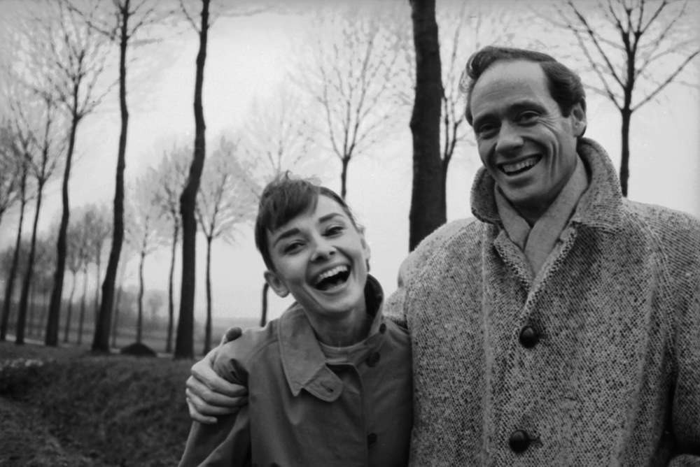 American actor Mel Ferrer (1917 - 2008) buttons up his coat around his wife, actress Audrey Hepburn (1929-1993), on a country road outside Paris, 1956. (Photo by Ed Feingersh/Michael Ochs Archives/Getty Images)