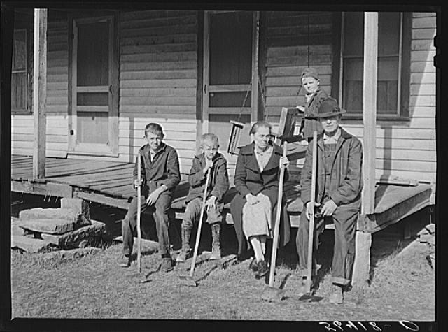 "Title: Dutton (""Dut"") Calleb and his family with their homemade hoes on the porch of their home. Southern Appalachian Project near Barbourville, Knox County, Kentucky Creator(s): Wolcott, Marion Post, 1910-1990, photographer Date Created/Published: 1940 Nov."