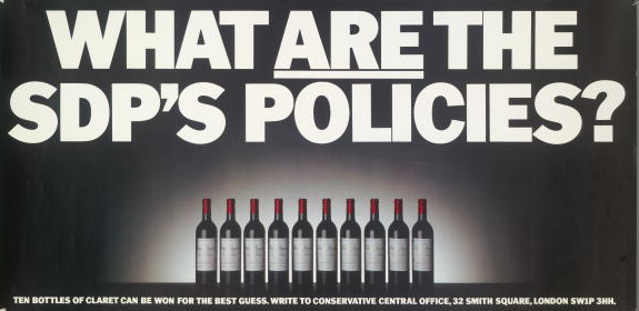A poster for the British Conservative Party from the 1983 General Election. It depicts a row of wine bottles with the caption 'What are the SDP's policies? Ten bottles of claret can be won for the best guess. Write to Conservative Central Office, 32 Smith Square, London SW1P 3HH'.