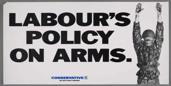 A poster for the British Conservative Party from the 1987 General Election. It depicts a British soldier with his arms up, and the caption 'Labour's policy on arms. Conservative - the next move forward'. Poster by advertising agency Saatchi & Saatchi.