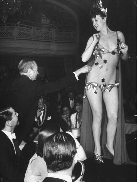 Famous burlesque star stripper Gypsy Rose Lee getting a $10 star plucked fr. her nude netting by wealthy mogul William Rhinelander Stewart during her show to raise money for the British War Relief Society, at the Astor Hotel