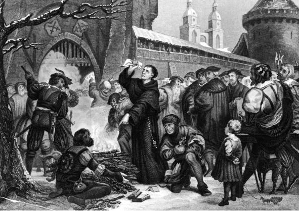 Circa 1518, Martin Luther standing before a fire with the work of Johann Tetzel in his hand. Tetzel and Luther wrote theological works arguing with the other's cause, resulting in the public burning of each other's wo