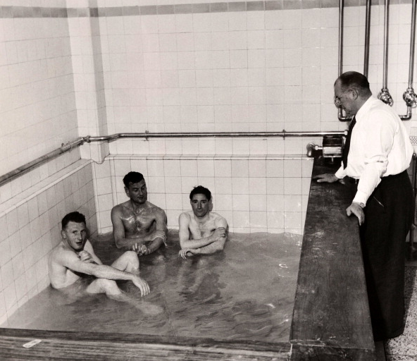 rsenal manager Tom Whittaker (right) talks to, left to right, Jimmy Logie, Alf Fields and Alex Forbes in the bath after a match at Highbury in London, circa November 1952.
