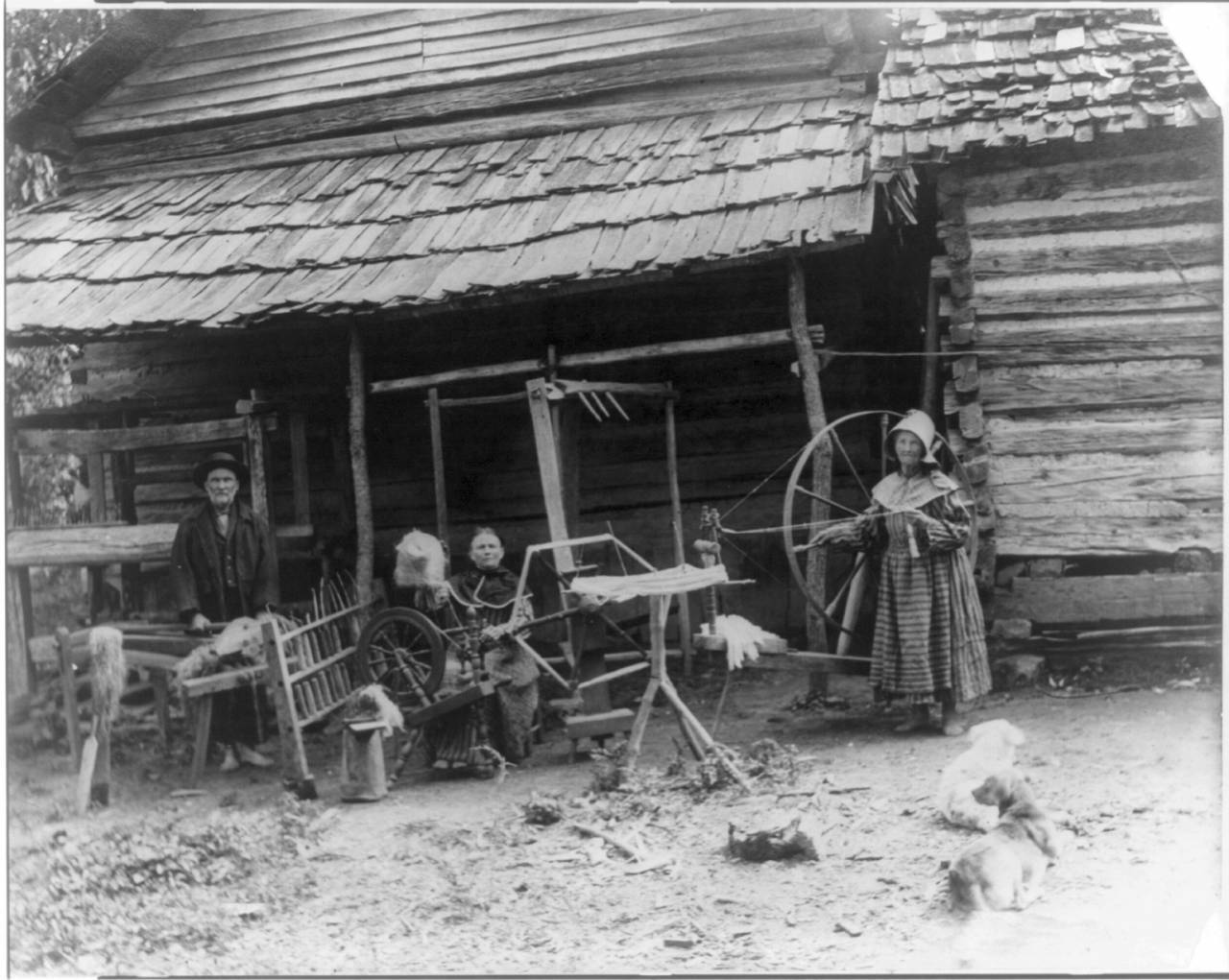 Title: The Faust family, Anderson County, Tenn. at spinning wheel in front of cabin Date Created/Published: c1910. Medium: 1 photographic print. Summary: Photograph shows people in front of a cabin processing and spinning flax. From right to left: Mary Faust standing next to large walking wheel, an umbrella swift, another woman seated at a spinning wheel with a distaff and a skein winder in front of her, and a man processing flax on a flax break with a counterbalance loom behind him.