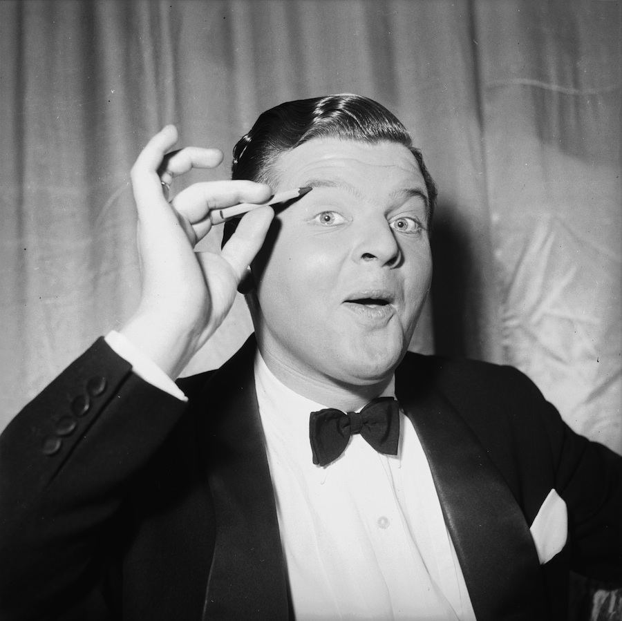 27th April 1956:  English comedian, Benny Hill (1925 - 1992), originally Alfred Hawthorne Hill, applying make-up to his eyes.  (Photo by Stroud/Express/Getty Images)