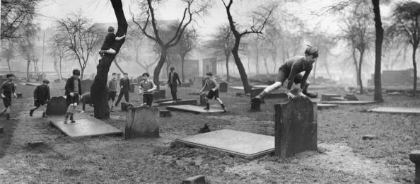 Kids laughed at death: Caption: A group of boys from the Gorbals play amongst the gravestones of the Corporation Burial Ground in Rutherglen Road, one of the few areas of greenery in the district.  1948.