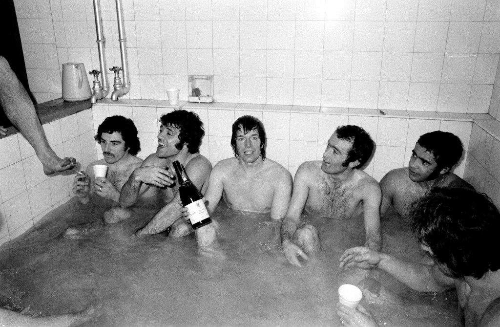 League Cup Semi Final Second Leg – Norwich City v Manchester United – Carrow Road Goal scorer Colin Suggett holds the bottle as Norwich players celebrate in the bath. With him are Colin Sullivan (far left), Peter Morris and Mel Machin (right). Date: 22/01/1975