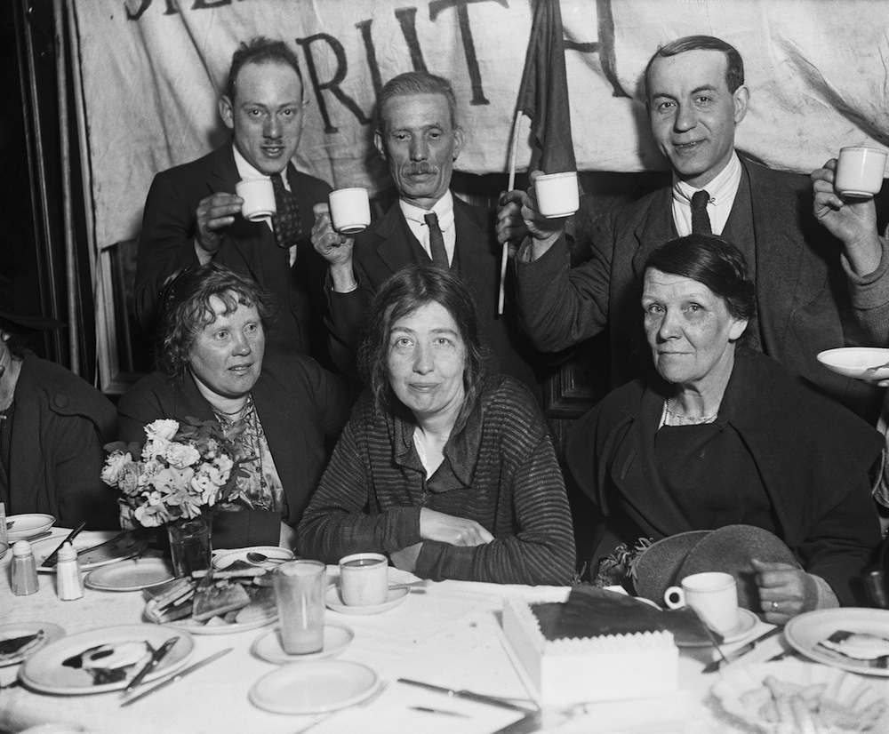 Supporters toast suffragette campaigner Sylvia Pankhurst (1882 - 1960, centre) at a breakfast to celebrate her release from prison, east London, May 1921. Pankhurst had been imprisoned since October 1920 for allegedly seditious articles in her Communist Party newspaper The Workers' Dreadnought. (Photo by Topical Press Agency/Hulton Archive/Getty Images)