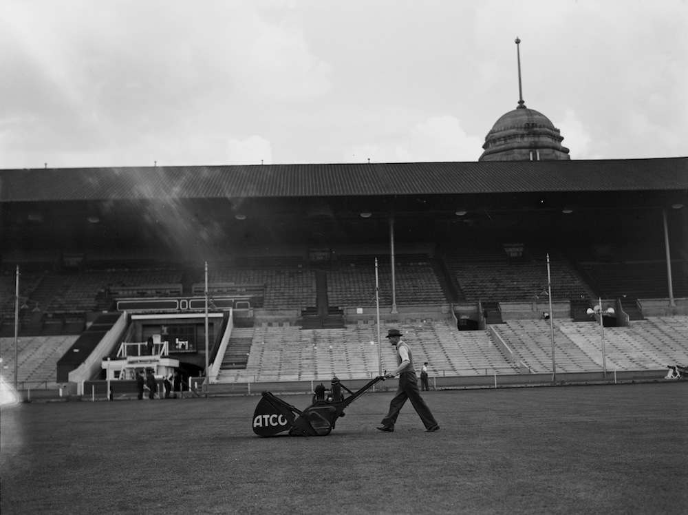 A groundsman mowing the pitch in preparation for the FA Cup final at Wembley Stadium, London, 29th April 1939. (Photo by H. F. Davis/Topical Press Agency/Hulton Archive/Getty Images)
