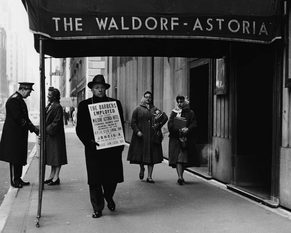 A lone hotel barber, a member of the AFL-CIO, carries a sign objecting to scab employees as he strikes outside the Waldorf-Astoria Hotel, New York City, 1940s. A uniformed doorman speaks to a woman in the background. (Photo by Corry/Getty Images)