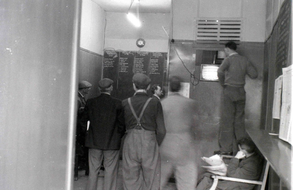 Illegal betting shop, Glasgow, 19 April 1960  I obtained this photo by looking behind a door where I saw suspicious characters entering and leaving. If I had been noticed, no doubt my camera would have been taken from me.