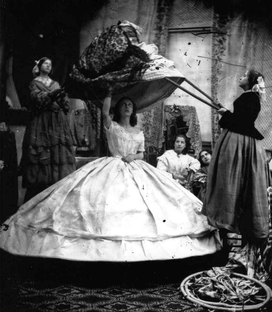 A woman  wearing a crinoline being dressed with the aid of long poles to lift her dress over the hoops.   (Photo by London Stereoscopic Company/Getty Images)