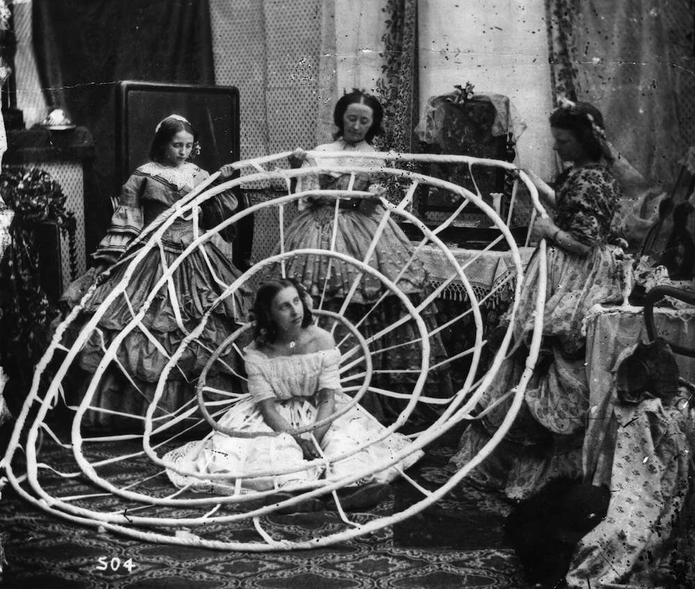 A young woman waits patiently whilst the hoops to support her crinoline are prepared. London Stereoscopic Company Comic Series - 504   (Photo by London Stereoscopic Company/Getty Images)