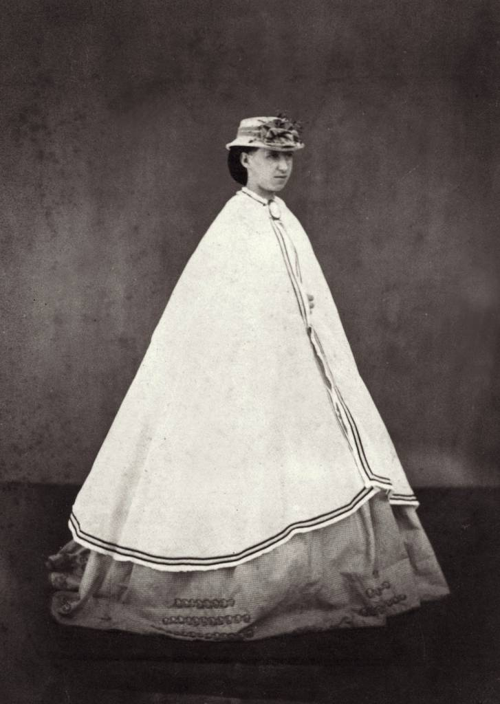 circa 1865:  A woman wearing a long cloak over her dress.  (Photo by Otto Herschan/Getty Images)