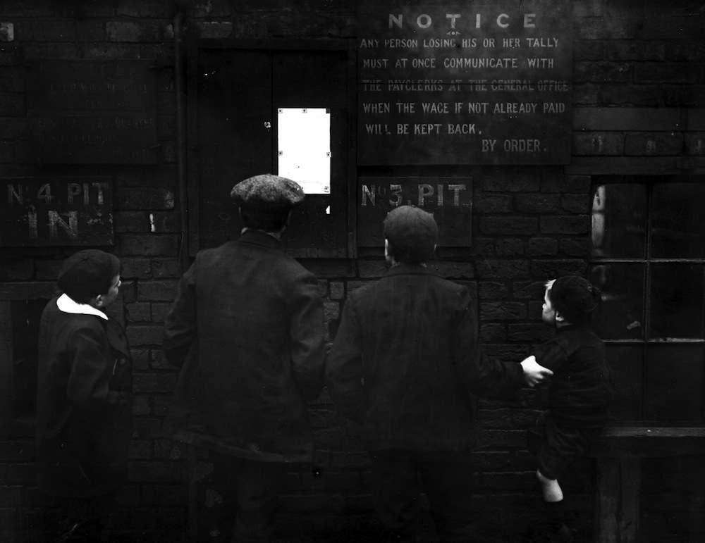 February 1912:  Young miners and their brothers read a notice outside a mine in Wigan during the miners' strike.  (Photo by Topical Press Agency/Getty Images)