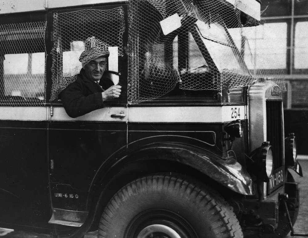 13th January 1936:  Portrait of the voluntary driver, Mr Burnett, on the Kettering to Rushden route, protected from attack by netting around his driving cabin. He replaces striking United Counties busmen in Northamptonshire.  (Photo by Fox Photos/Getty Images)