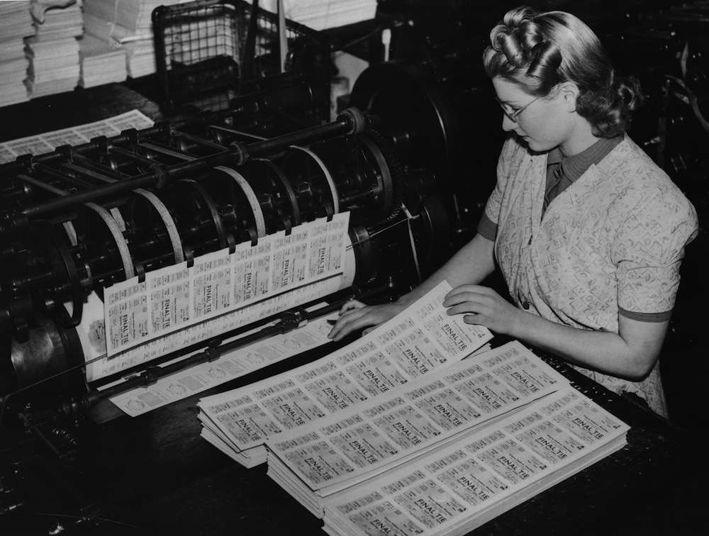6th February 1939: A young woman checks tickets for the FA Cup Final as they come off the press. (Photo by Fox Photos/Getty Images)