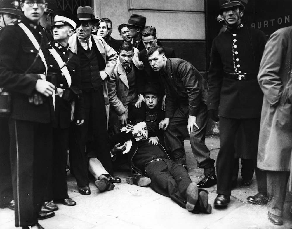 11th October 1936:  Attending to an injured man following the riots in Victoria Park, London, where the Communists converged after their march through the East End.  (Photo by Fox Photos/Getty Images)