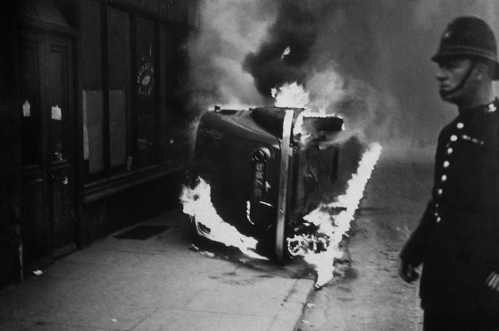 circa 1936:  A policeman stands by a burning car, set alight during a communist march in the East End of London.  (Photo by Topical Press Agency/Getty Images)