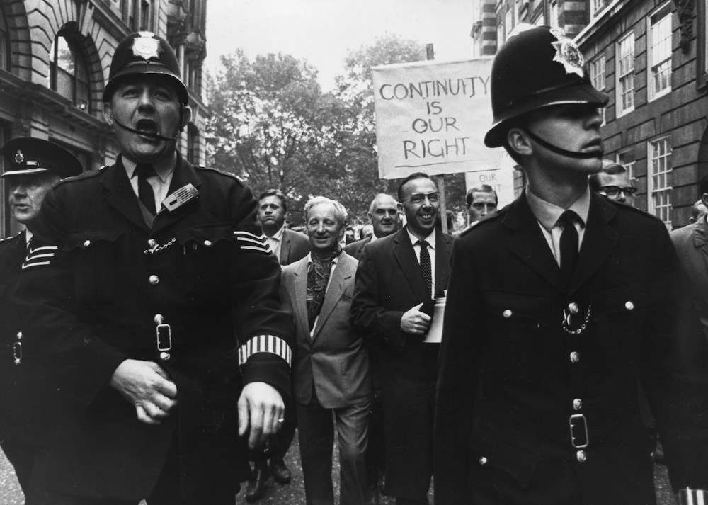 10th October 1967: Unofficial dock leader, Communist Jack Dash framed between two policemen who were guarding the march of striking dockers on their way to Transport House in London. (Photo by Jim Gray/Keystone/Getty Images)