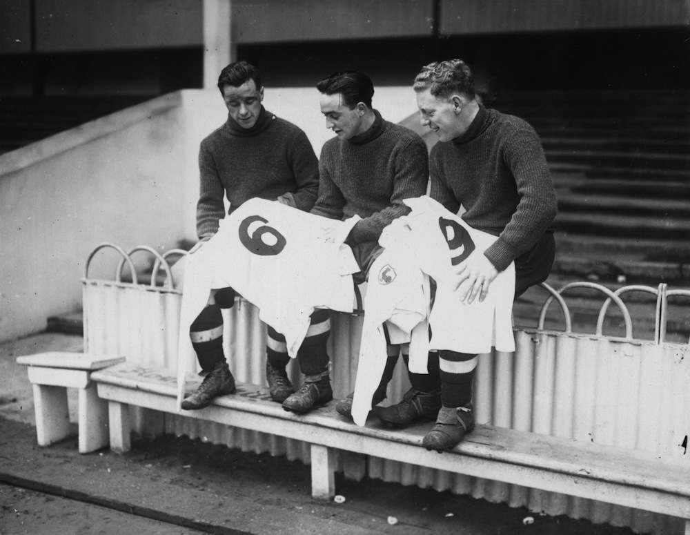 3rd January 1939:  Three Tottenham Hotspur FC soccer players looking at their new numbered football shirts for the third round FA cup tie against Watford at White Hart Lane, London. Left to right Duncan, A Hall, and W Hall (Capt).  (Photo by Stephens/Topical Press Agency/Getty Images)