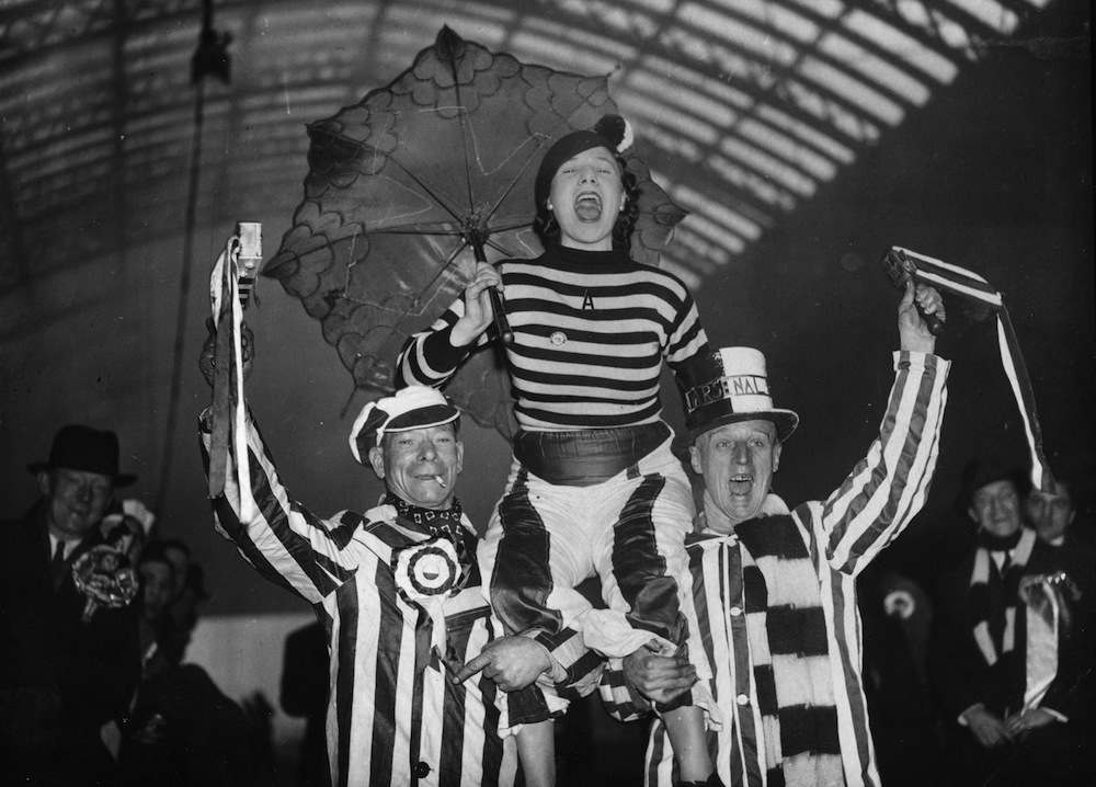 16th January 1937:  Arsenal football supporters cheering for their team at St Pancras Station, London, as they make their way to Chesterfield.  (Photo by E. Dean/Topical Press Agency/Getty Images)