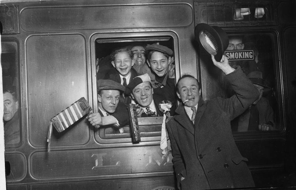 19th November 1932:  Arsenal football supporters cheering from the train carriage window as they leave Euston Station, London, on their way to Birmingham for their team's match against Aston Villa which they lost 3 - 5.  (Photo by Douglas Miller/Topical Press Agency/Getty Images)