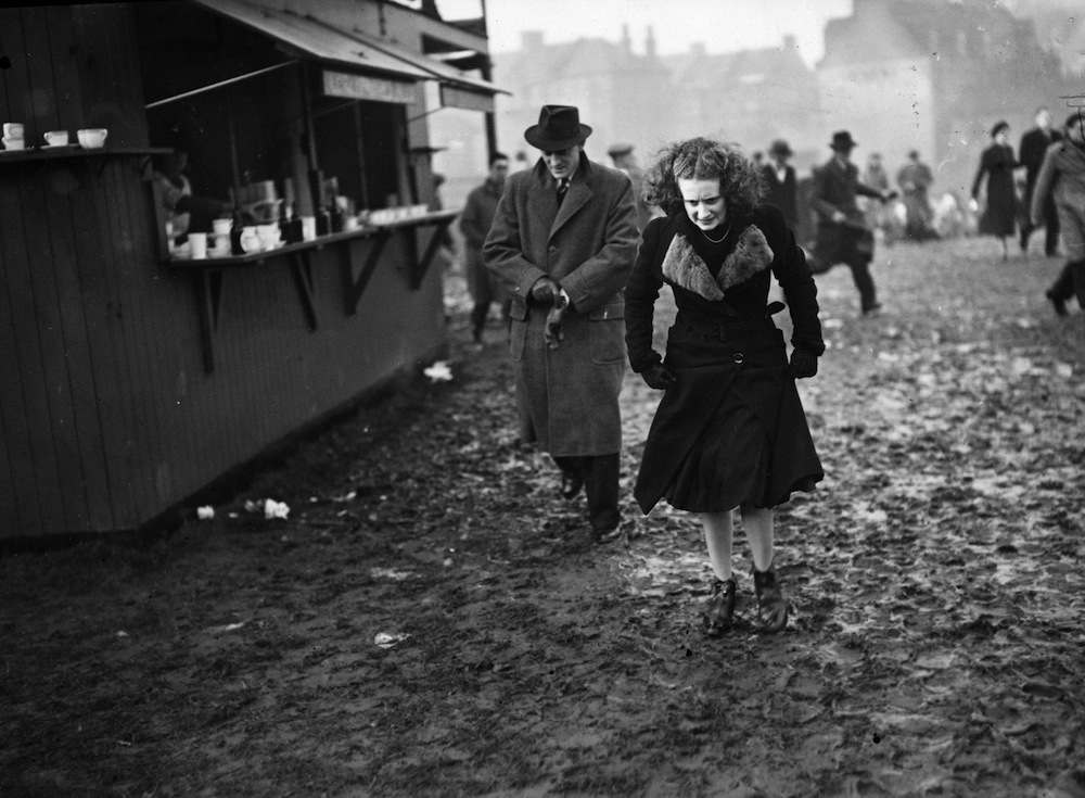 27th December 1938:  Football fans making their way through the slush of melted snow on their way to watch Charlton Athletic play Arsenal.  (Photo by H. F. Davis/Topical Press Agency/Getty Images)