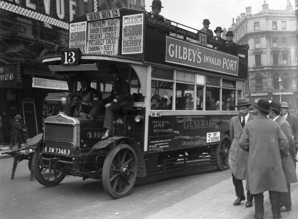 18th May 1926:  An LGOC bus being driven in London by a volunteer driver with a police escort during the General Strike, May 1926.  (Photo by Davis Snr/Topical Press Agency/Getty Images)