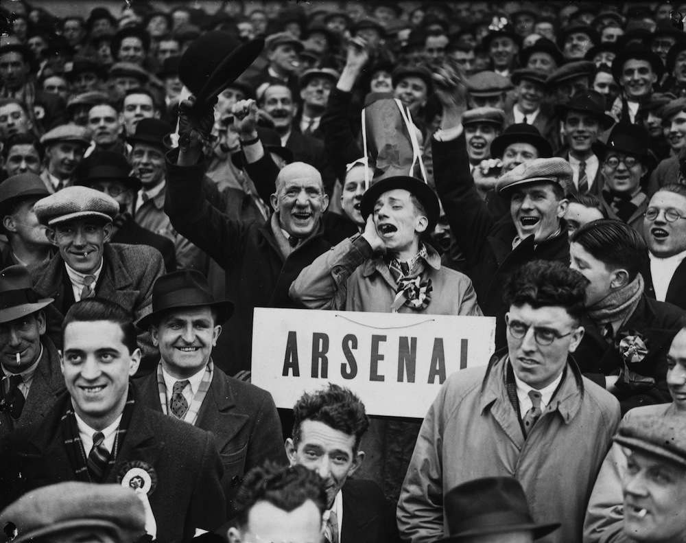 22nd January 1938:  An Arsenal football club supporter declares his allegiance with a large sign during a match against Wolverhampton Wanderers.  (Photo by Topical Press Agency/Getty Images)