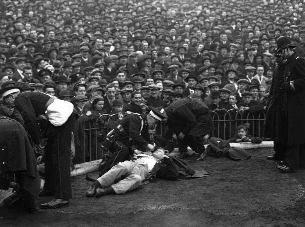 31st January 1934:  Ambulance men attending to some of the spectators who fainted in the crush at Arsenal FC ground at Highbury when a huge crowd turned up for the Arsenal versus Tottenham Hotspur match.  (Photo by A. Hudson/Topical Press Agency/Getty Images)