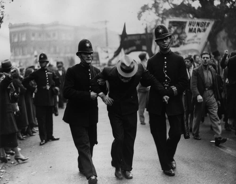 11th October 1936:  Two policemen making an arrest during a rally at Clapton Square, Hackney, London. A group of Fascists held a mass meeting at one end of the street, and a group of Communists at the other, resulting in inevitable clashes.  (Photo by Fox Photos/Getty Images)