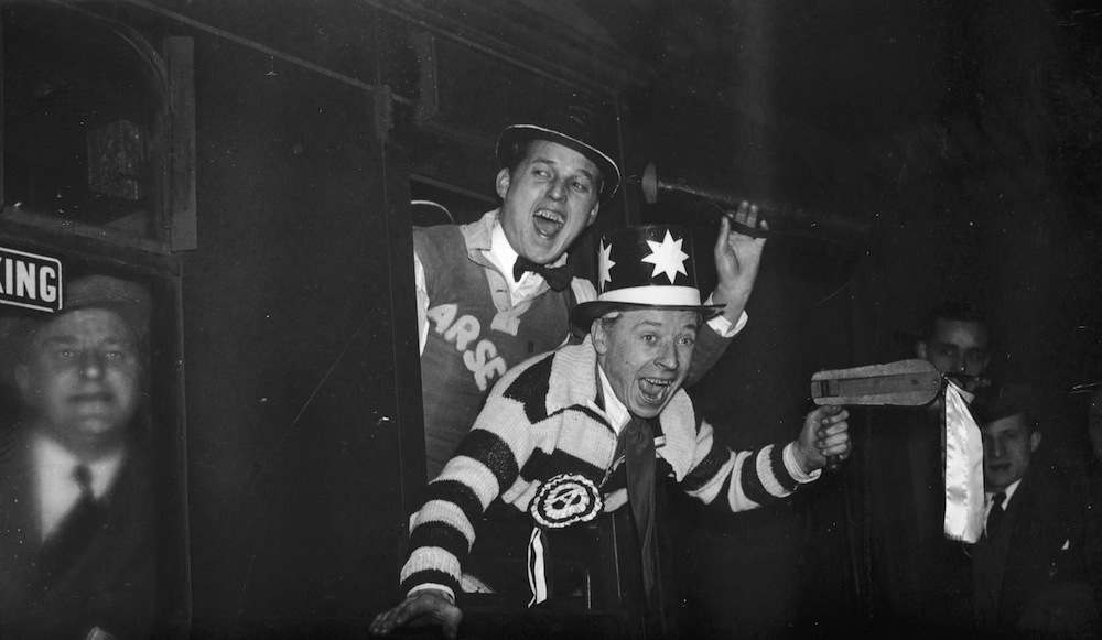 Arsenal fans wearing team colours leave Euston Station, London, on the way to see their team play Wolverhampton Wanderers in the F A Cup, 22nd January 1938. Arsenal lost the tie 3-1. (Photo by E. Dean/Topical Press Agency/Getty Images)