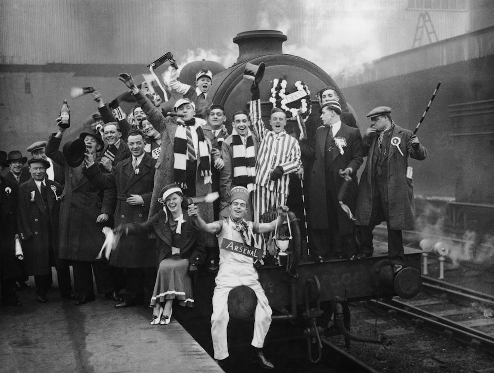 Arsenal fans at King's Cross to catch the special trains to Huddersfield for the F A Cup semi final against Grimbsy, 21st March 1936. Arsenal won 1-0.  (Photo by E. Dean/Topical Press/Getty Images)