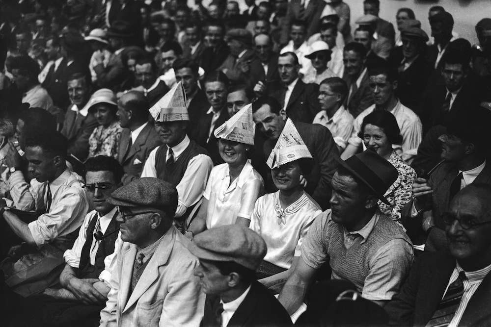 Football supporters wearing newspaper hats to shelter from the sun at Highbury during Arsenal vs Everton, the opening game of the season, 29th August 1936. (Photo by J. A. Hampton/Topical Press Agency/Getty Images)