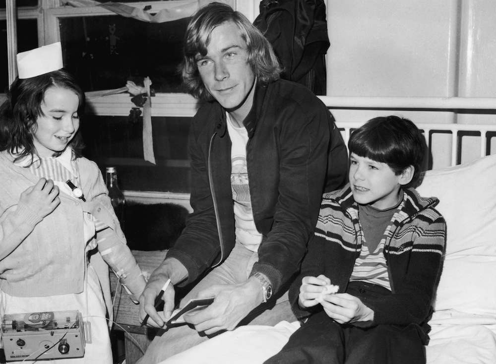 English racing driver James Hunt (1947 - 1993) with patients Lynn Boyce and Tyrone Wyman during a visit to Great Ormond Street Children's Hospital, London, 3rd February 1977. (Photo by Monti Spry/Central Press/Hulton Archive/Getty Images)
