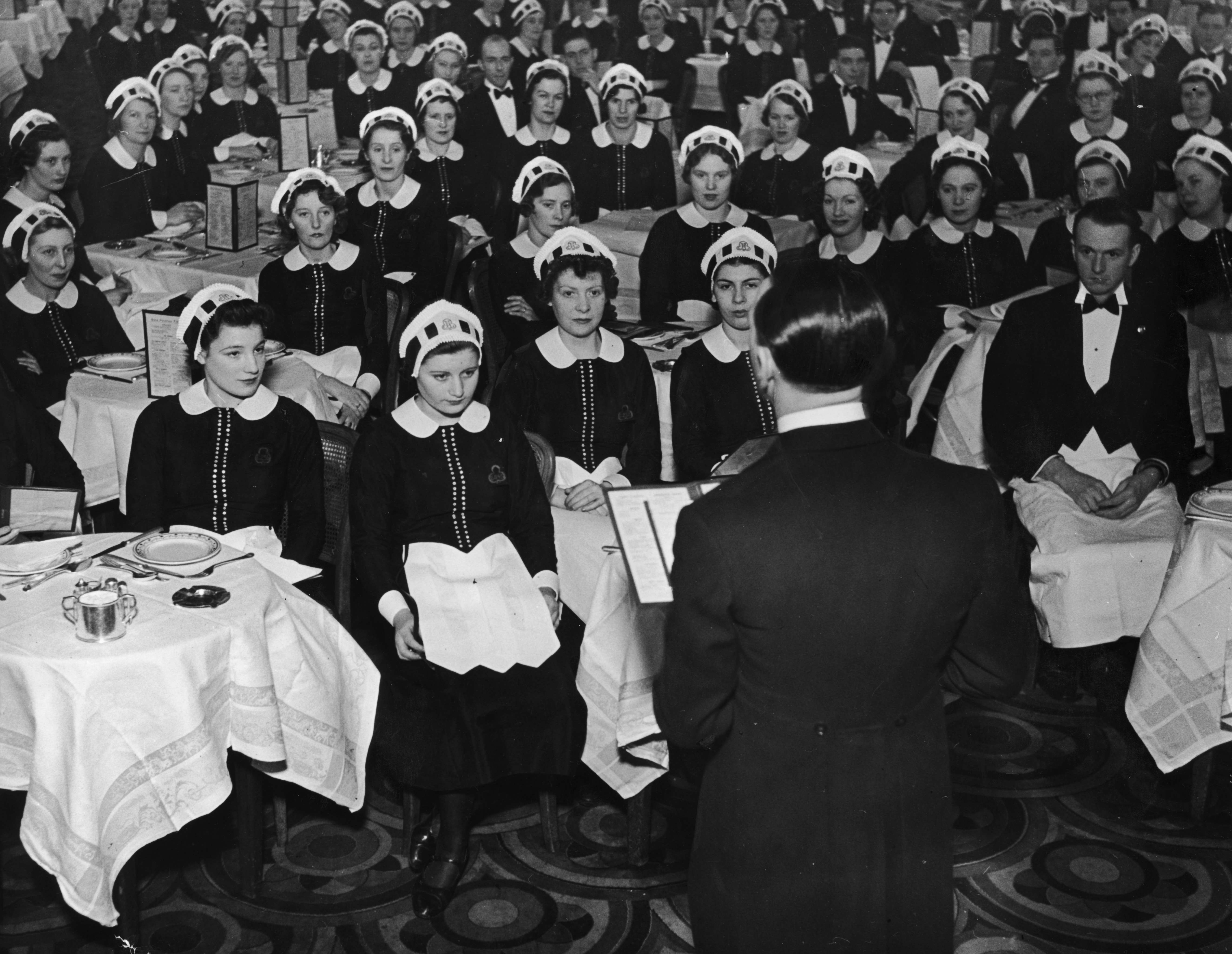 4th March 1939:  Waitresses, known as Nippies, at Lyon's Corner House in London receiving their instructions at the start of the day.  (Photo by Bill Brandt/Picture Post/Getty Images)