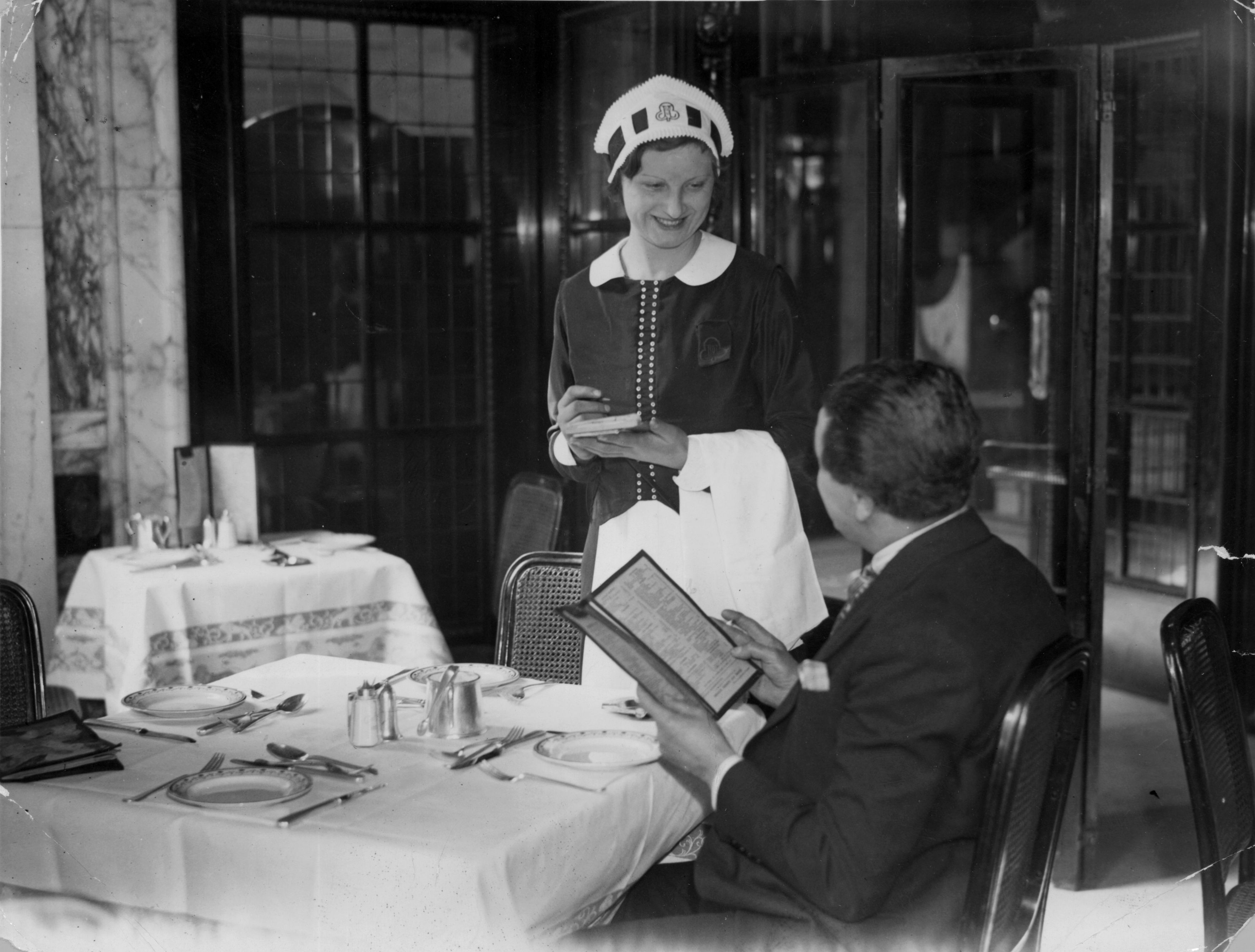 5th April 1935:  Miss B Lillywhite, a 'nippy' at Coventry Street Corner House in Piccadilly is ready to take an order from a customer.  (Photo by Miller/Topical Press Agency/Getty Images)