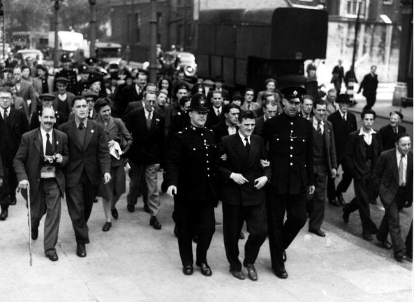 12th September 1946, Tommy Horton a member of the Holborn Communist Party in London being taken away by police after being arrested after he and a group squatted illegally in the Ivanhoe Hotel, London